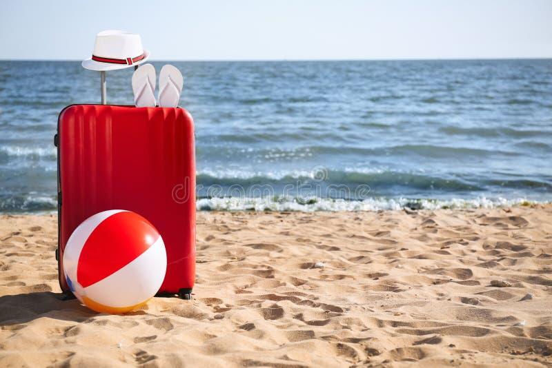 Jaskrawa walizka i różni plażowi akcesoria na piasku blisko morza przestrze? zdjęcia stock