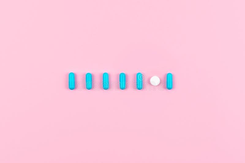 Jaskrawe błękitne pigułki w linii, rząd na różowym tle Medycyny, leki, apteki pojęcie Mieszkanie nieatutowy, odgórny widok, minim zdjęcia stock