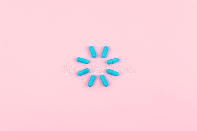 Jaskrawe błękitne pigułki w obciążeniowym symbolu na różowym tle Medycyny, leki, apteki pojęcie Mieszkanie nieatutowy, odgórny wi obraz stock