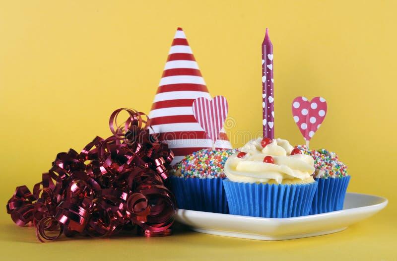 Jaskrawe i radosne czerwone temat babeczki z urodzinową świeczką błękitne i żółte obraz stock