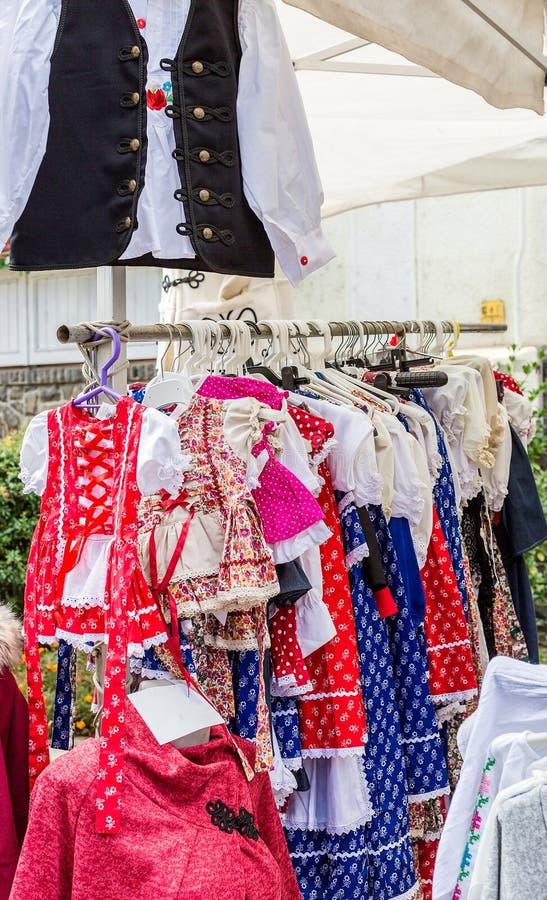 Jaskrawego krajowego węgra odzieżowy obwieszenie na wieszakach w ulicznym sklepie obrazy stock