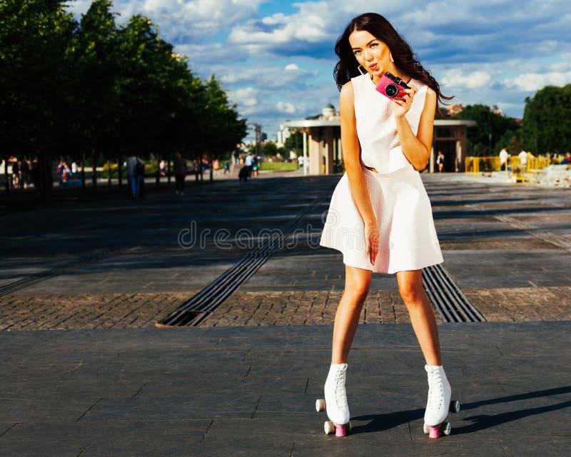 Jaskrawego lato portreta azjatykcia dziewczyna w lato jaskrawym stroju pozuje na rolkowych łyżwach z różową rocznik kamerą bierze zdjęcia stock