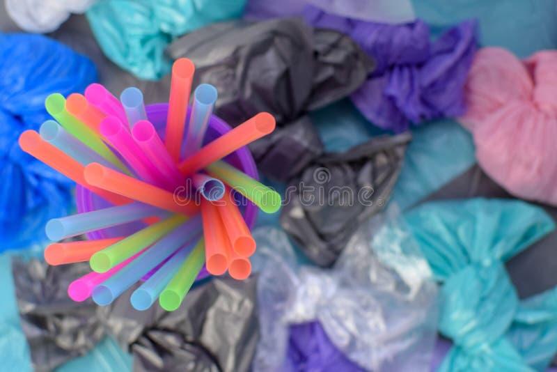 Jaskrawi barwiący plastikowi tubules w purpurowym szkle na tle torby na śmiecie fotografia royalty free