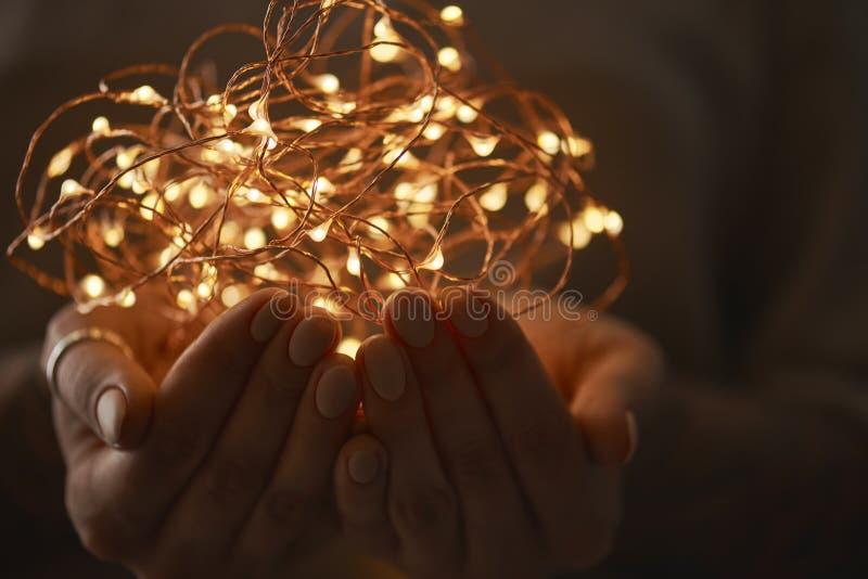 Jaskrawi bożonarodzeniowe światła w kobiety ` s rękach obraz royalty free