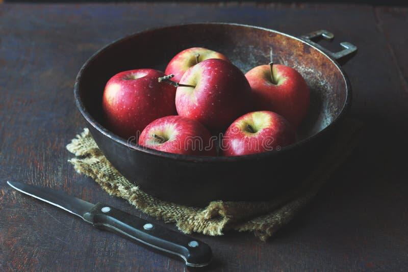 Jaskrawi czerwoni jabłka w kruszcowej smaży niecce zdjęcia stock