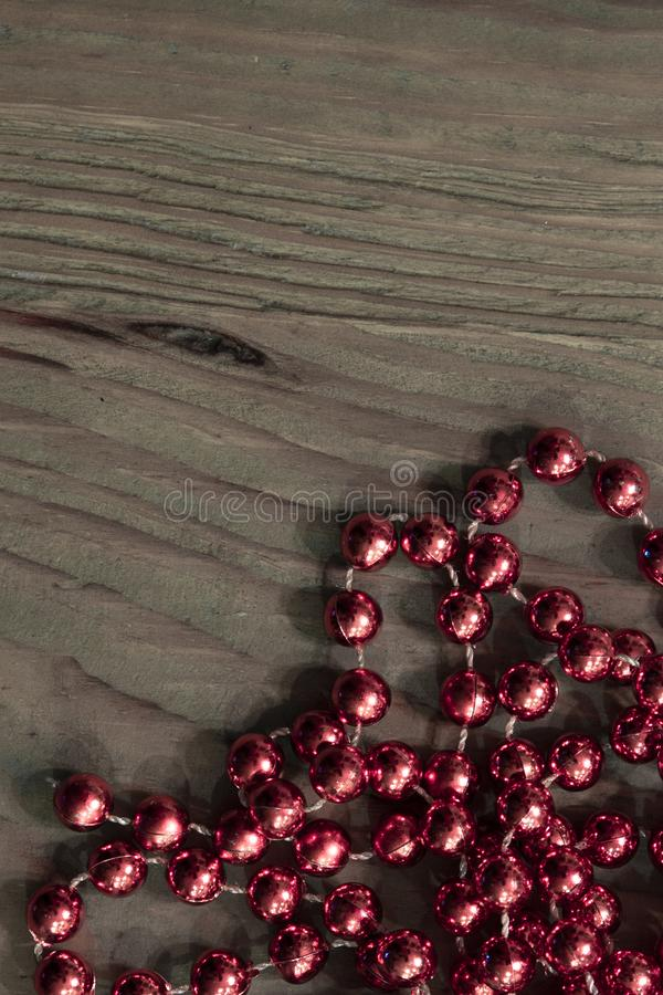 Jaskrawi czerwoni kruszcowi koraliki na nieociosanym drewnie ukazuj? si? zdjęcia stock