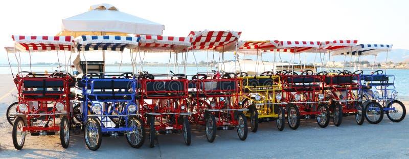Jaskrawi czterokołowi bicykle z pasiastymi sukiennymi dachami zdjęcia royalty free