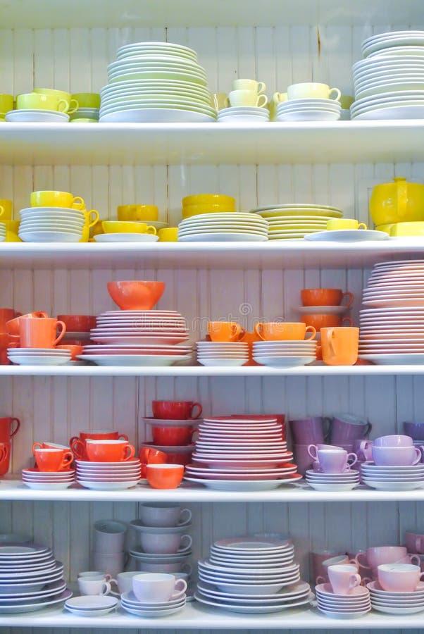 Jaskrawi naczynia, talerze i filiżanki stoi na w kolorowi żółci czerwieni, zdjęcie royalty free