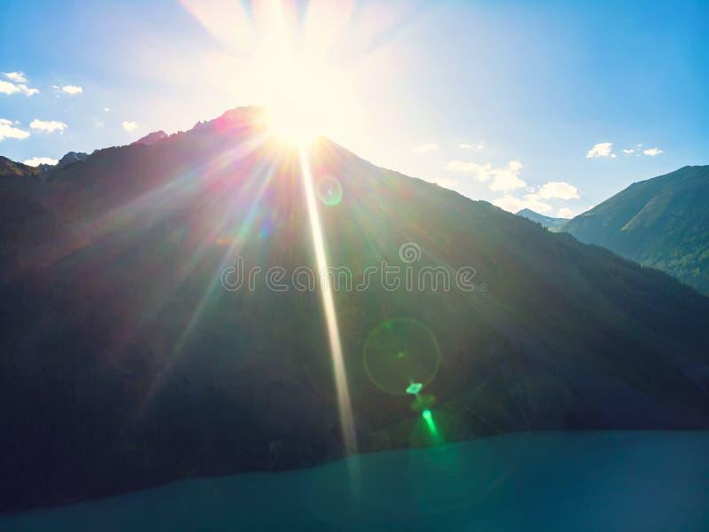 Jaskrawi pomarańczowi słońce promienie nad halnym jeziorem, wschód słońca nad górą Jaskrawi słońce promienie robią ich sposobowi  obraz royalty free
