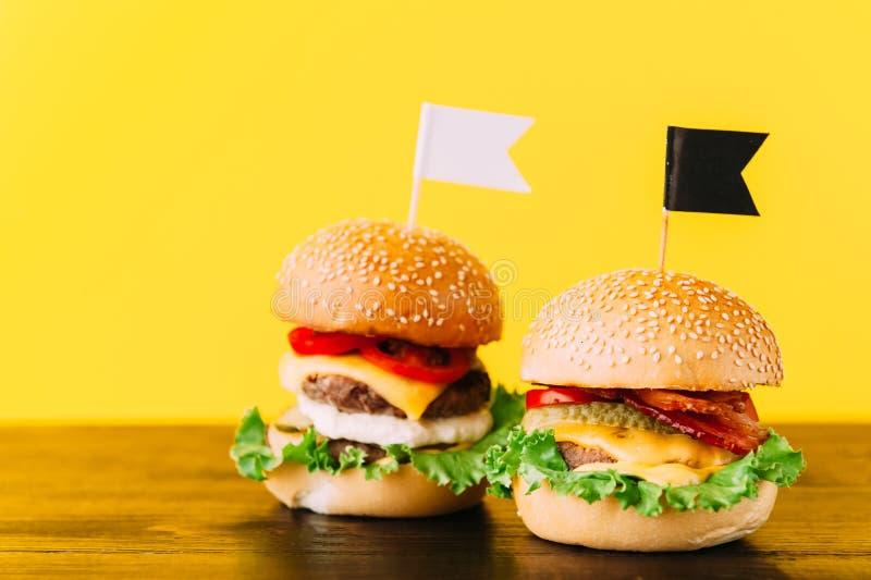 Jaskrawi soczyści apetyczni hamburgery z kotlecikami, serem, marynowanymi ogórkami, pomidorami i bekonem, obraz royalty free
