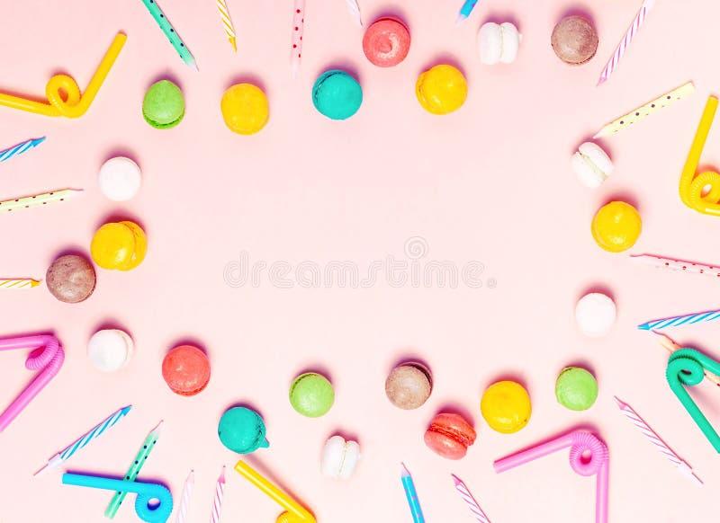 Jaskrawi urodzinowi akcesoria, candels i macarons na różowym tle, obraz stock