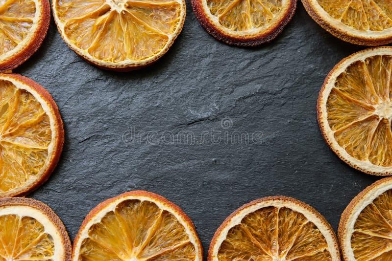 Jaskrawi wysuszeni pomarańcze plasterki na kamiennym textured tle, kopii przestrzeń, mieszkanie nieatutowy, odgórny widok zdjęcia stock