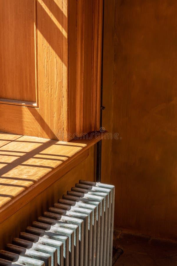 Jaskrawy światło od okno leje się przez ciepłego drewnianego windowsill i rocznika metalu grzejnika fotografia royalty free