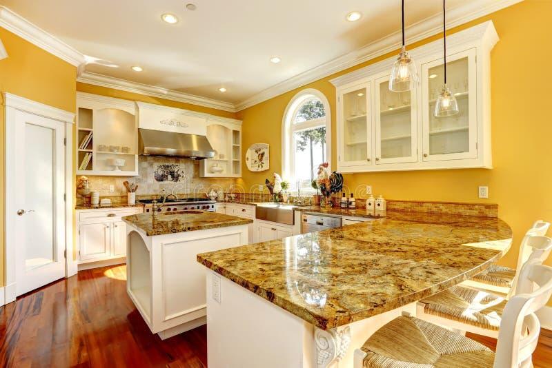 Jaskrawy żółty kuchenny pokój z granitowymi wierzchołkami zdjęcie royalty free