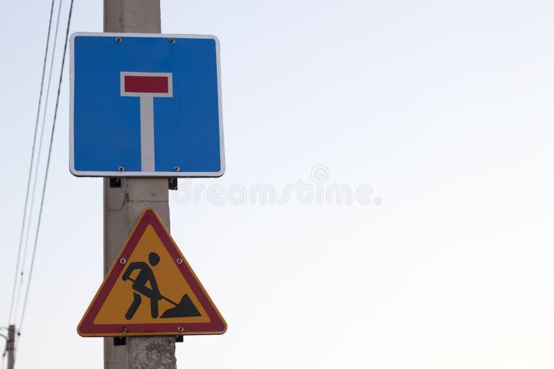 Jaskrawy żółty trójgraniasty znak ostrzegawczy; Uwaga, praca naprzód i martwy koniec ulica na kwadratowej błękitnej osłonie na be zdjęcia royalty free