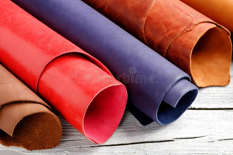 Jaskrawy barwiąca skóra w rolkach na drewnianym tle Rzemienny rzemiosło obraz royalty free
