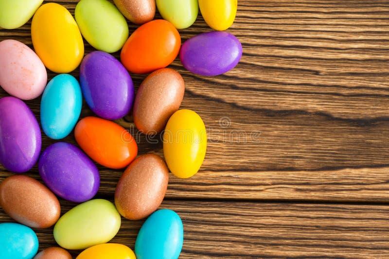 Jaskrawy barwiący cukierów pokryci migdały na drewnie fotografia royalty free