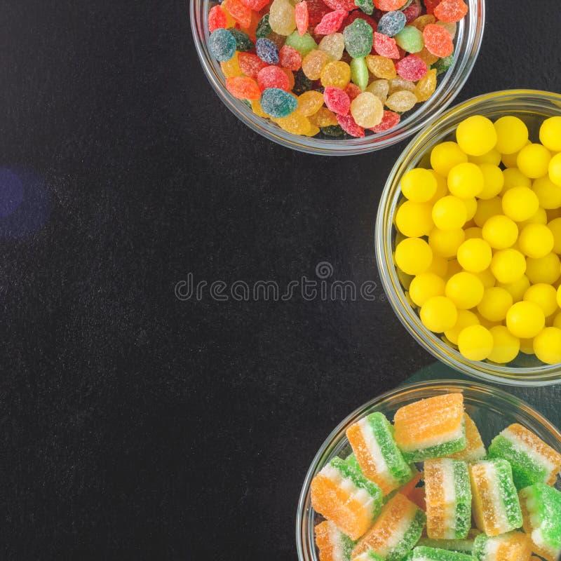 Jaskrawy barwiący cukierki w szklanych filiżankach na czarnym stole, odgórny widok fotografia royalty free