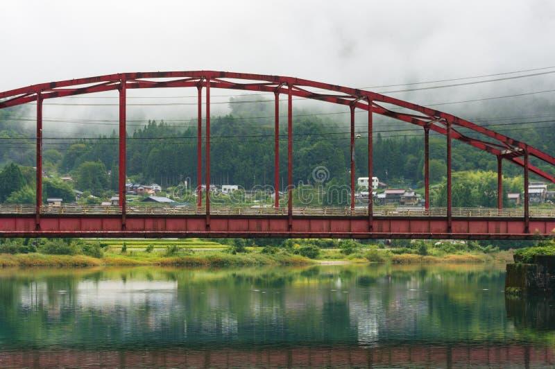 Jaskrawy czerwień łuku most nad malowniczą rzeką w Japońskim countr obraz royalty free