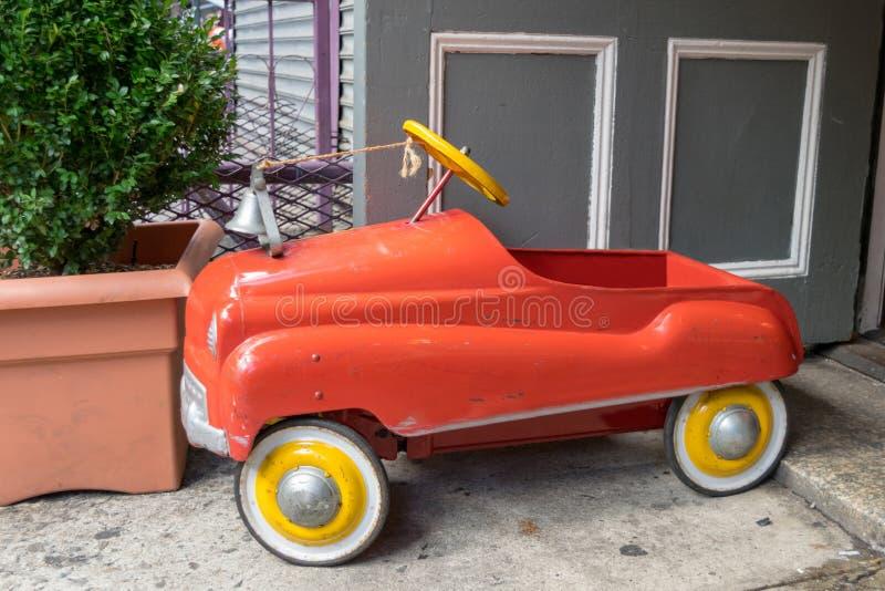 Jaskrawy czerwieni & koloru żółtego zabawkarski samochód strażacki stoi za againsta ponurym siwieje betonowego środowisko fotografia royalty free