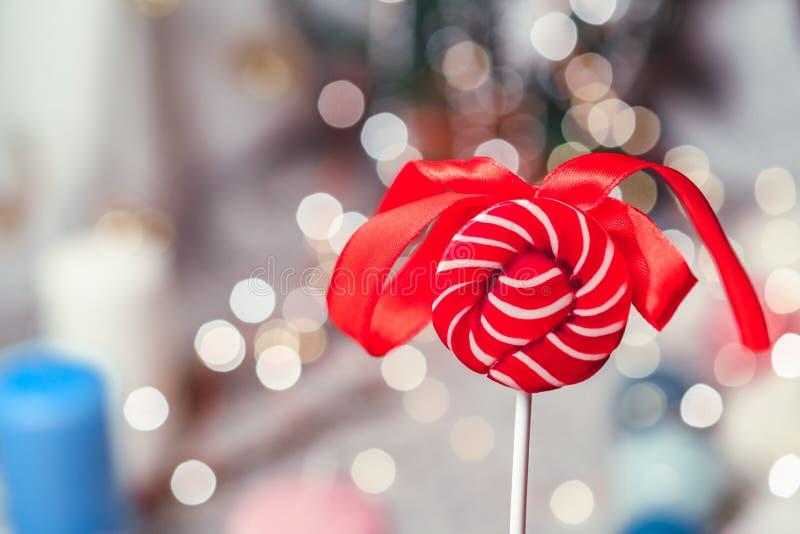 Jaskrawy czerwony round cukierek z łękiem przeciw tłu bokeh obraz royalty free
