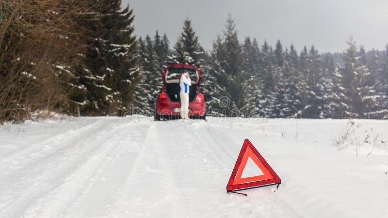Jaskrawy czerwony trójbok na śnieżnej drodze ostrzega innych kierowców zdjęcia royalty free
