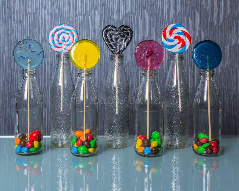 Jaskrawy i kolorowy lollipopÑ ‹w jasnych butelkach stoi na szkło stole obraz royalty free