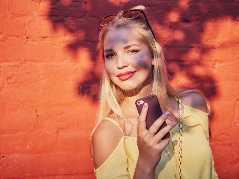 Jaskrawy i kolorowy zakończenie w górę portreta młoda piękna blondynki kobieta z wysokiej babeczki fryzury żółtą bluzką cieszy si obrazy royalty free