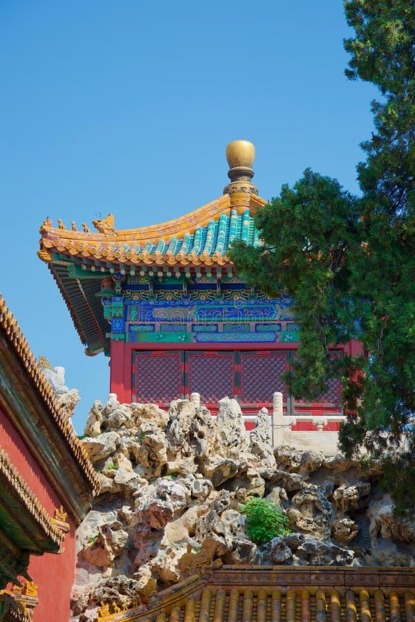 Jaskrawy malująca Chińska pagoda w ogródzie z rockery i drzewem obrazy stock