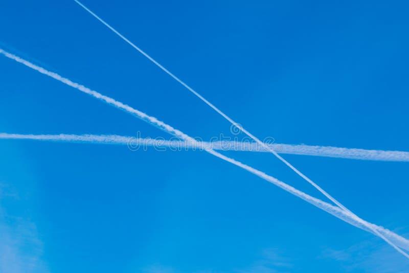 Jaskrawy niebieskie niebo z liniami chmury - ślada od samolotu zdjęcia royalty free