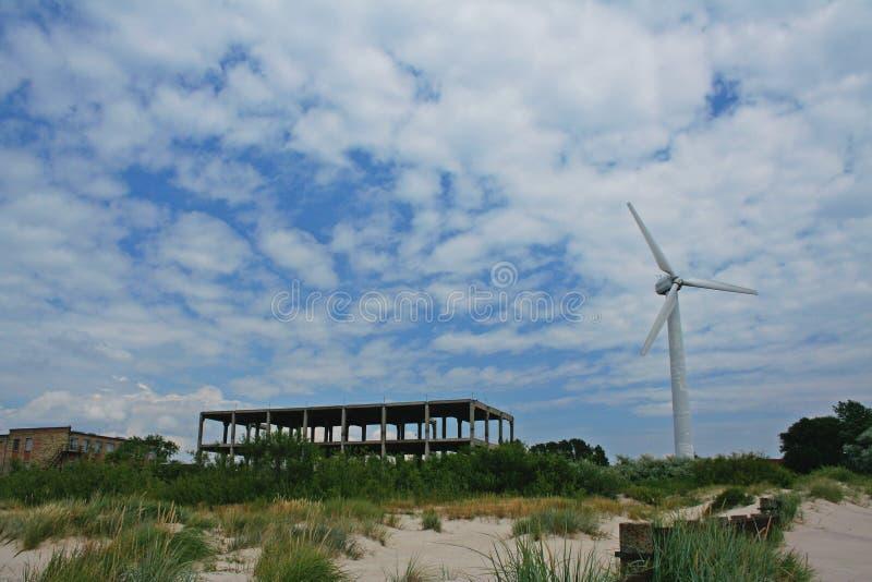 Jaskrawy obrazek silnik wiatrowy pozycja w piasku blisko niedokończonego budynku zdjęcie stock