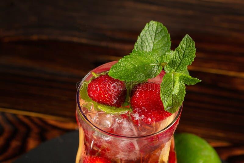 Jaskrawy odświeżający stawberry koktajl z mennicą, lodem i kawałkami truskawka, Lato napój odizolowywający na drewnianym tle obraz royalty free