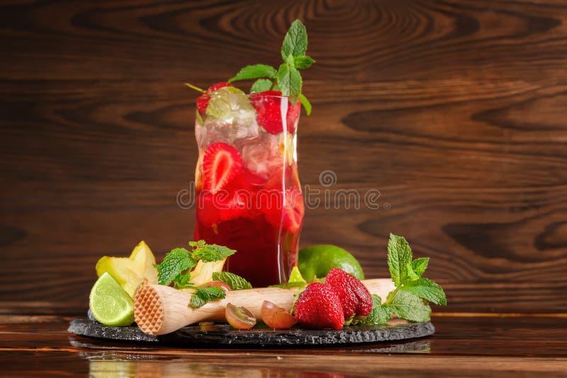 Jaskrawy odświeżający stawberry koktajl z mennicą, lodem, plasterkami wapno i kawałkami truskawka, Lato napoje kosmos kopii zdjęcie stock