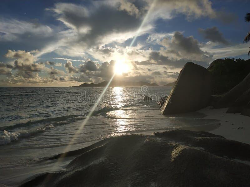 Jaskrawy olśniewający zmierzch przy Ladigue Seychelles z lekkim promieniem fotografia stock