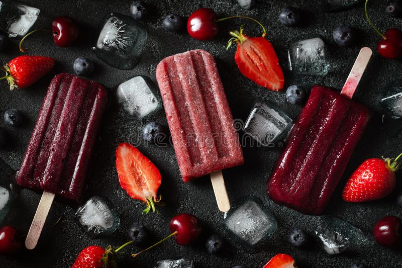 Jaskrawy popsicle robić wiśnie, truskawki i czarne jagody, na zmroku betonujemy tło S?odka lato funda Odg?rny widok mieszkanie zdjęcie stock