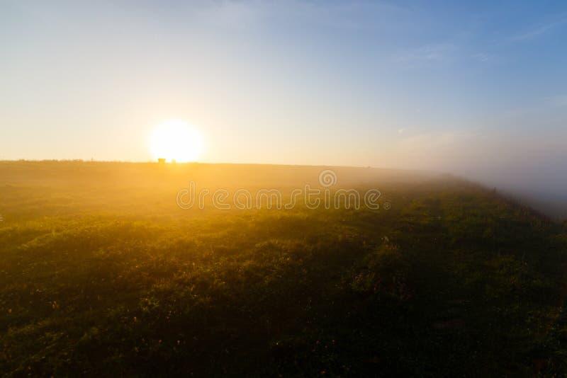 Jaskrawy słońca jaśnienie przy horyzontem nad mgłowymi skłonami obraz royalty free