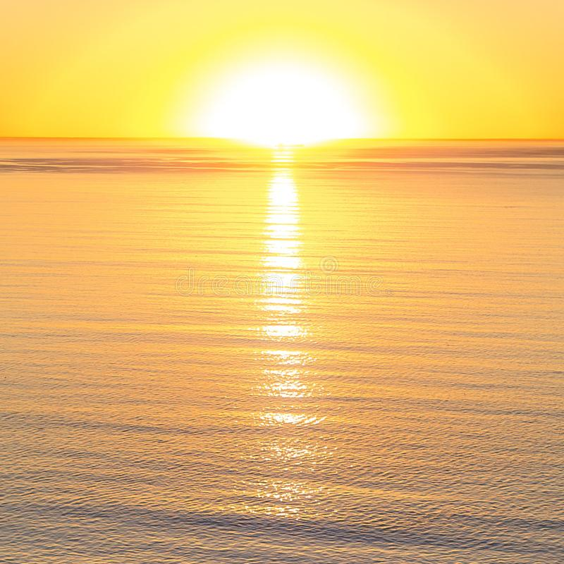 Jaskrawy słońce odbijał w spokojnej wodzie przy zmierzchem obrazy royalty free