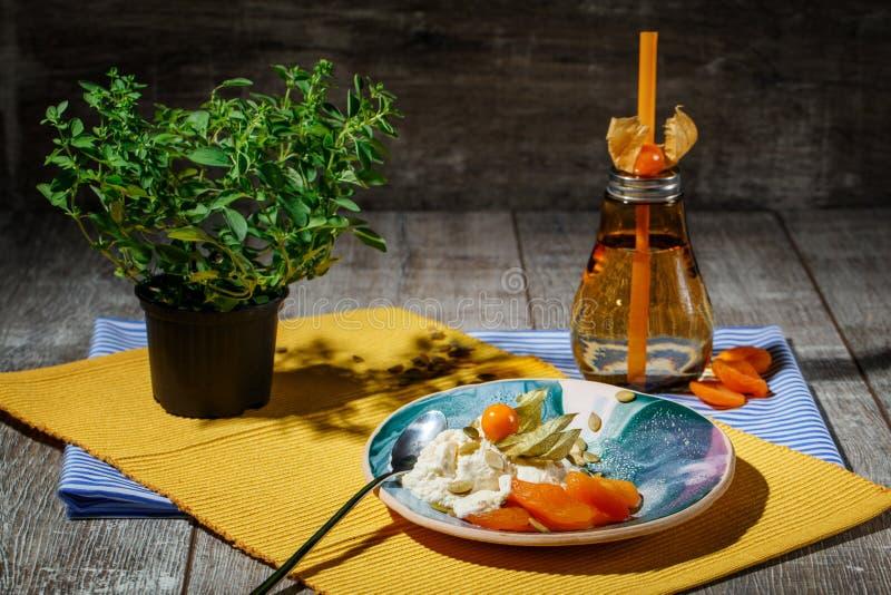 Jaskrawy skład round talerz, pomarańczowa butelka i zielony sapling, Śliczny obiadowy ustawiający na drewnianym tle obraz royalty free