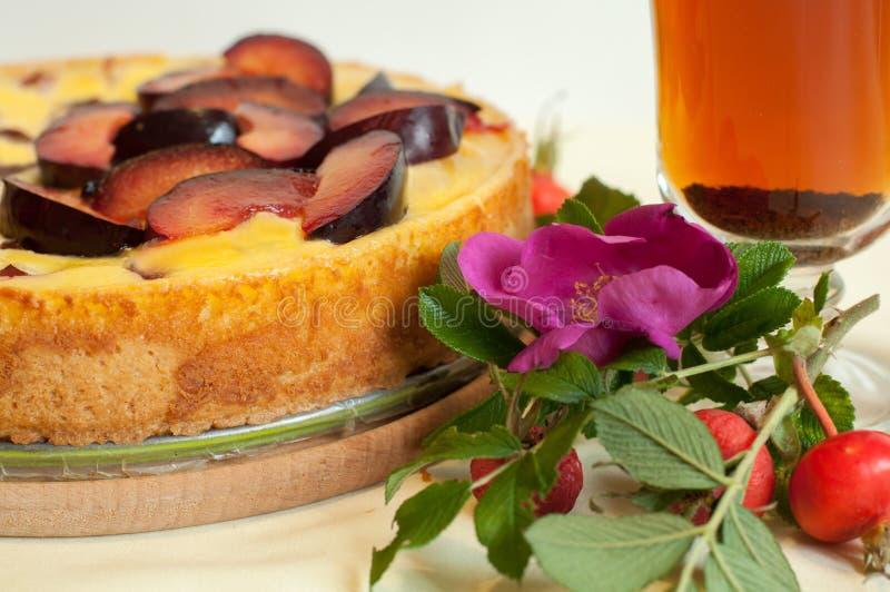 Jaskrawy skład z owocowym kulebiakiem, szklaną filiżanką herbata, świeżym psem różanym i biodrami, obrazy stock