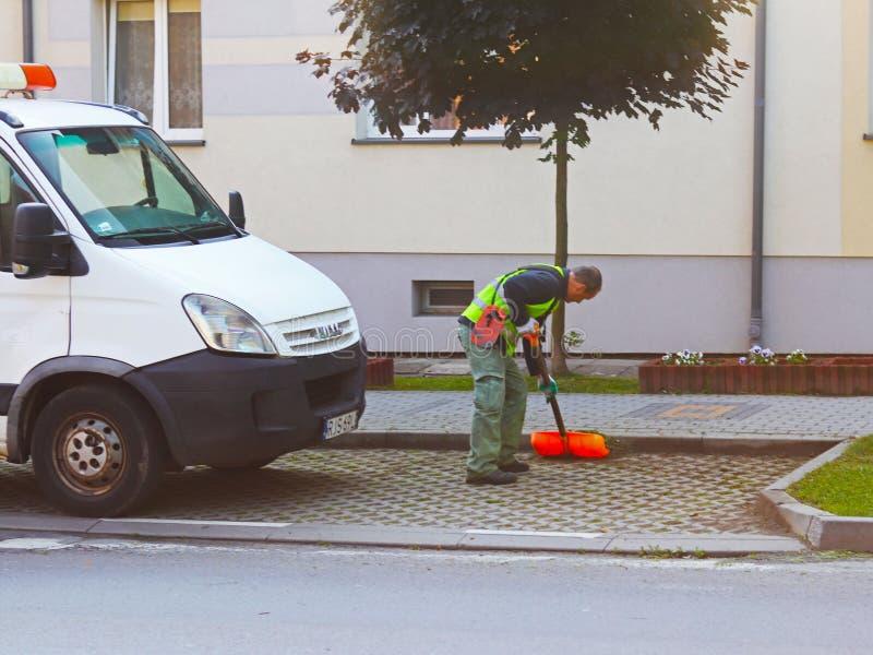 Jaslo, Polônia - podem 25 2018: Um empregado do serviço municipal da cidade remove o território Refinamento da área ao redor imagens de stock royalty free