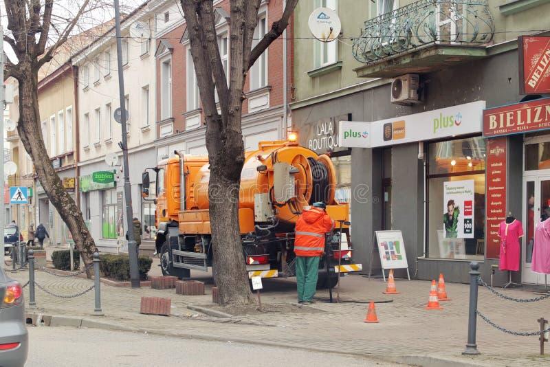 Jaslo, Polen - 3 9 2019: Angestellte des städtischen Services pumpten Schmutz vom Stadtabwasserkanal unter Verwendung eines Autos lizenzfreies stockfoto