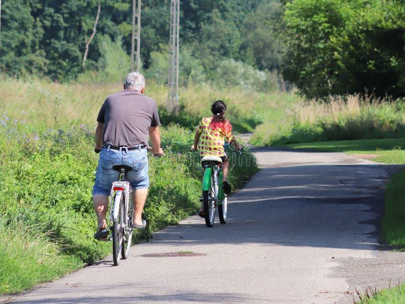 Jaslo Polen - 9 juli 2018: Fader- och dotterritten cyklar längs asfaltvägen under sommargräsplanerna i strålarna av royaltyfri bild
