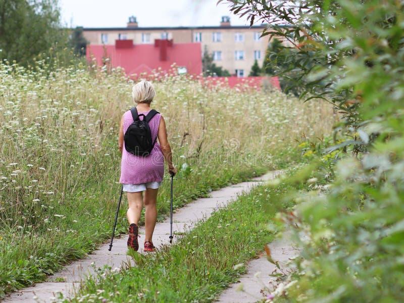 Jaslo, Polonia - 9 de julio de 2018: Escandinavo/el caminar nórdico Una mujer en ropa de la ciudad da un paseo a través de la hie foto de archivo