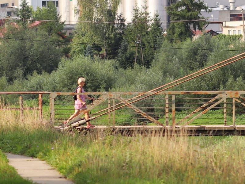 Jaslo, Polonia - 9 de julio de 2018: Escandinavo/el caminar nórdico Una mujer en ropa de la ciudad da un paseo a través de la hie foto de archivo libre de regalías