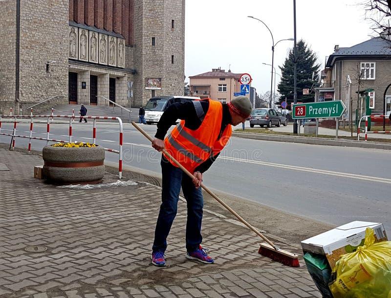 Jaslo/Polonia-marcha 27,2018: El portero en su ropa de funcionamiento barre la acera Limpieza del territorio en la ciudad El wor imagenes de archivo