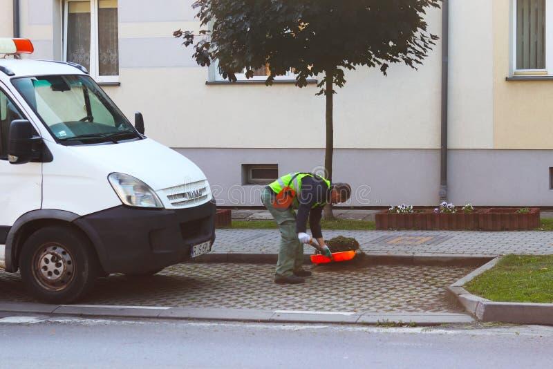 Jaslo, Polonia - puede 25 2018: Un empleado del servicio municipal de la ciudad quita el territorio Refinamiento del área alreded foto de archivo libre de regalías