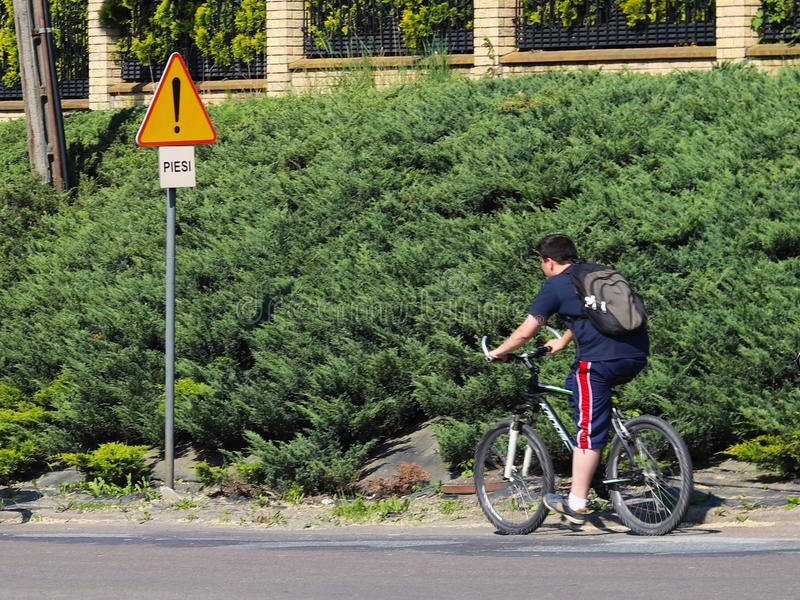 Jaslo/Yaslo, Poland - may 22,2018: Road sign danger on the highway. safety of traffic. Two guys riding bicycles in summer`s sunny stock photos