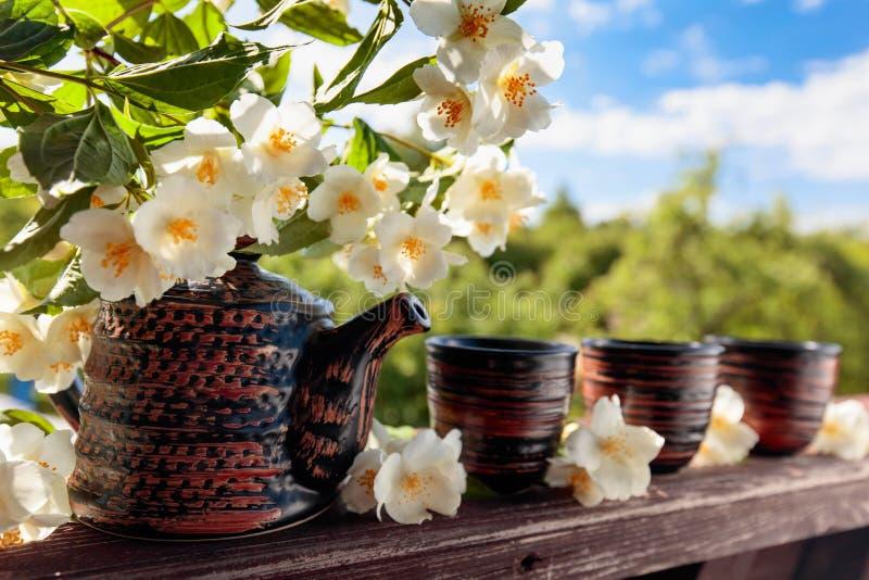 Jasmijnthee in kleine ceramische koppen op oude houten lijst in tuin  stock afbeeldingen