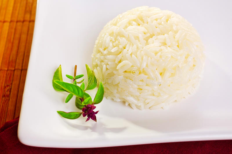 Jasmine Rice and Thai Basil. A moulded mound of jasmine rice on a white plate, and a sprig of Thai basil stock image