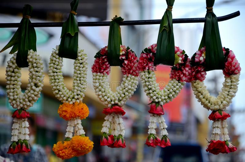 Jasmine and rose flower garlands hang with banana leaves in bazaar Hatyai Thailand. Hatyai, Thailand - May 6, 2017: A collection of beautiful flower garlands royalty free stock photography
